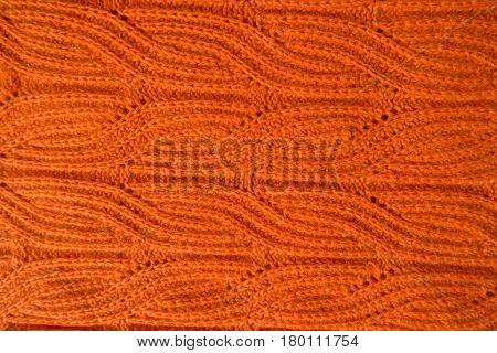 Bright orange handmade knit fabric with plait pattern