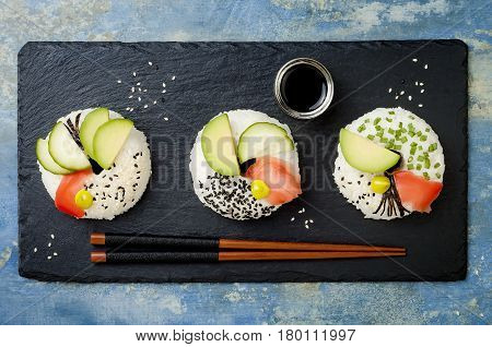 Vegan sushi donuts set with pickled ginger avocado cucumber chives nori and sesame served on stone slate. Sushi-food hybrids trend. Overhead top view flat lay.
