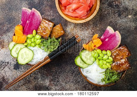 Vegan tofu poke bowls with seaweed watermelon radish cucumber edamame beans and rice noodles. Copy space background overhead flat lay