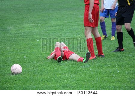 Injured player at the football match lying on the grass