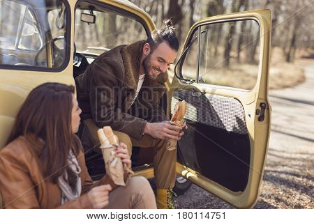 Young couple taking a break on their road trip sitting in the car by the road and eating sandwiches
