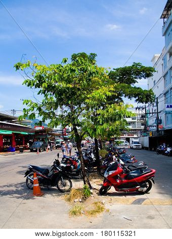Patong. Thailand. January 31 2017: Motor scooters parked under trees next to the market.