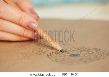 Close-up shot of female hand holding pencil, sketchbook with unprofessional depiction of flower lying on table