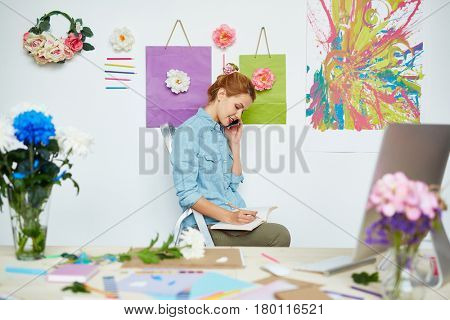 Blond-haired florist in denim shirt sitting on stepladder, talking to her client on smartphone and taking notes with pencil, abstract painting and flower decorations hanging on wall