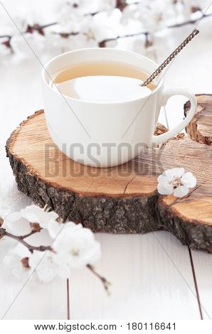 White cup of hot tea with spring flowers on a light wooden background. Herbal tea Lifestyle Spring Breakfast Light background with flowers.