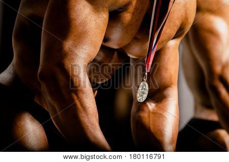 awarding of gold medal winner on man chest athlete bodybuilder
