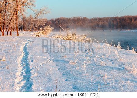 The river bank is covered with snow in which the trgopinka is trodden. Water of the river soars from a frost and branches of trees are covered with hoarfrost.