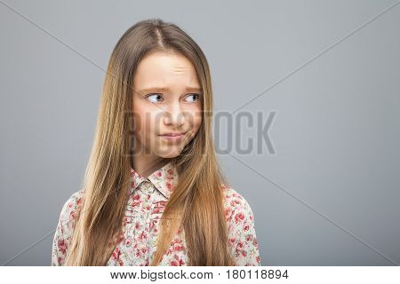 young blond pretty girl in hipster shirt looking disregard at something. Concept of disrespect, negation, rejection, reluctance, unwillingness