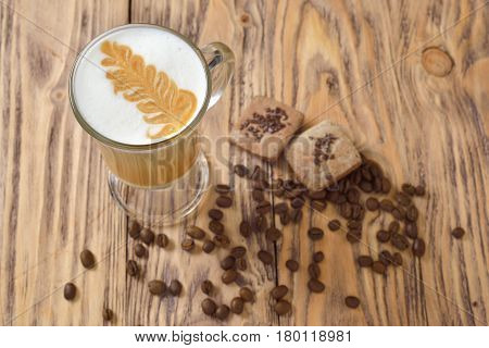coffee in glass mug coffee beans and cookies on a wooden worktop