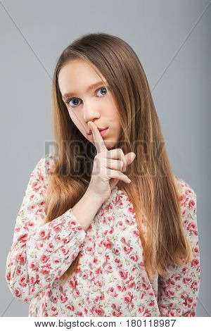 Woman requires silence. Young beautiful blond girl has put forefinger to lips as sign of silence. Concept of secret, silence