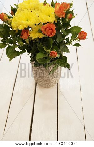 Vase Of Flowers On A White Rustic Table. Top View. Rustic Vase With Orange Roses And Yellow Chrysant