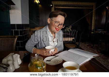 attractive girl in glasses with a short hairstyle in the interior of a stylish cafe reads a book and drinks tea. Intelligent person.
