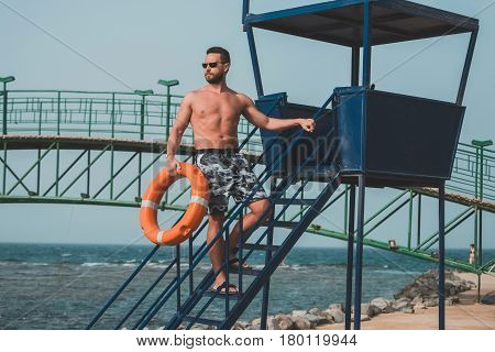 bearded lifeguard muscular man with muscle torso with orange ring buoy for life saving on duty on tower overlooking sea ocean beach sunny summer day on blue sky background. Safety rescue vacation