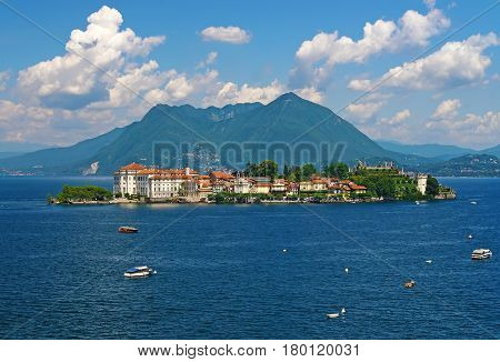 Scenic view of Bella Island - Isola Bella - on Maggiore lake - Lago di Maggiore Italy at sunny summer day with boats in lake water on foreground and Alp mountains and picturesque clouds on background