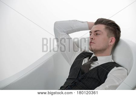 Handsome man or businessman with stylish haircut hair in fashion business wear vest tie and shirt relaxing in bath tub isolated on white background