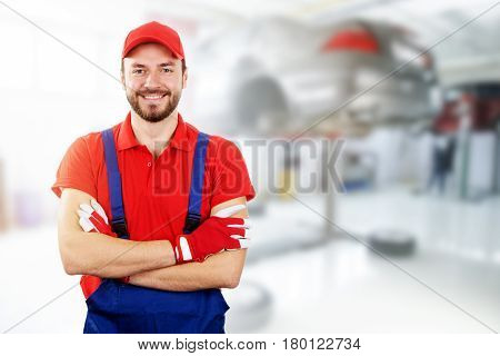 happy auto mechanic standing in car service garage