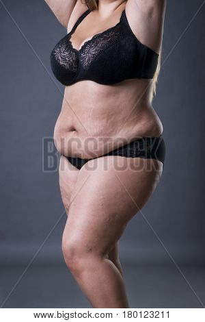 Woman with fat abdomen overweight female stomach stretch marks on belly gray studio background