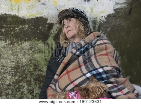 Mature homeless woman leaning against an old wall