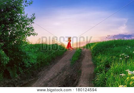 Young woman in the red dress is dancing far on a dirt path in a green field in the rays of the setting sun.
