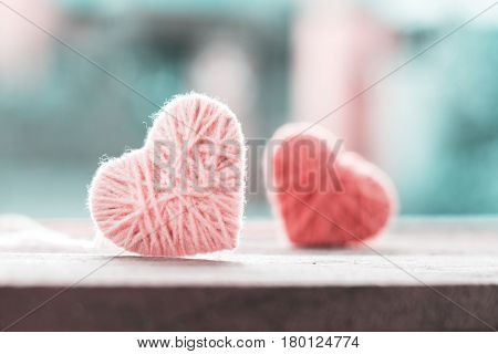 soft color knitting wool in shape of heart on vintage wooden with bokeh soft light background