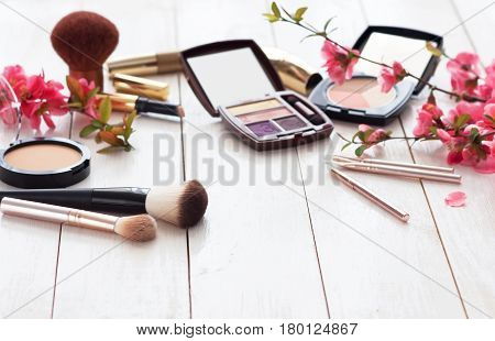 Various cosmetic products for make-up with pink flowers on a white wooden background with copy space. poster