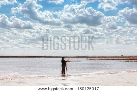 A man by the lake among the reeds in a quartz sand quarry with a distant horizon and a beautiful cloudy sky.