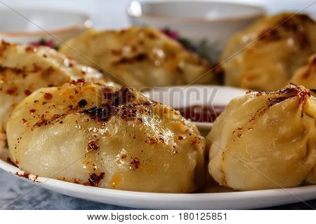 Manti on a plate with sauce. Traditional food of the inhabitants of Central Asia. Closeup