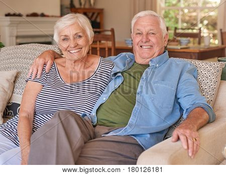 Portrait of a smiling senior man with his arm around his wife's shoulder sitting happily together on their living room sofa at home