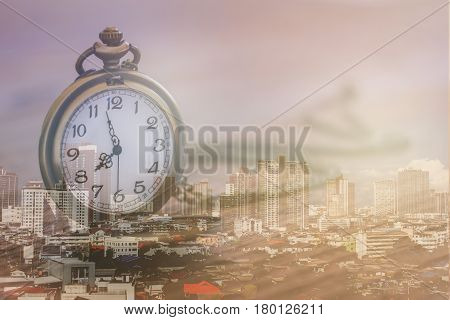 pocket watch over town center with double exposure effect time is make money in town business finance and competition concept