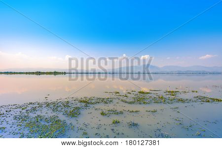 calmness lake in the morning with mountain and reflection in the water Kwan Phayao or Phayao Lake Northern of Thailand