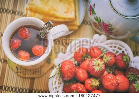 Crepes and Fresh strawberry tea in white cup teapot ripe strawberries in a vase and crepes. Breakfast composition for country family in the morning top view. Image with filter effect instagram