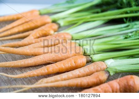 Fresh and sweet carrot on wooden table Bunch of fresh carrots with green leaves over wooden background Vegetable Food