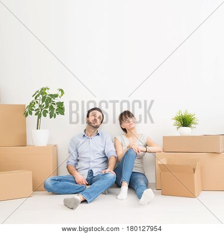 A young couple sitting on the floor and looking up. Dream and enjoy your new home.