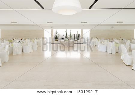 Table of the couple in the middle and tables of guests at the sides in a white room set up for the event to understand a concept of life with love