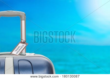 Suitcase with travel insurance label on blurred sea background.