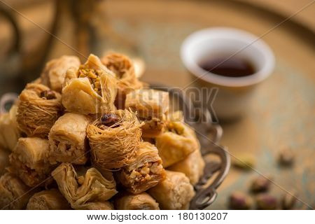 Assorted baklava- A Turkish sweet arranged on  a decorative plate, with arabic black coffee cup in the background. Middle eastern food photography.