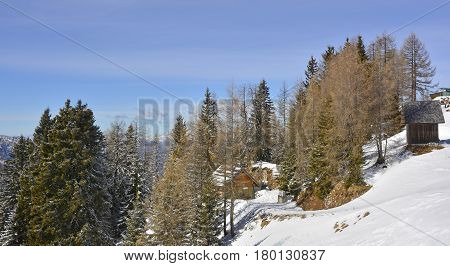 Small wooden huts and trees in the snow on the slopes of Monte Lussari Friuli Venezia Giulia north east Italy