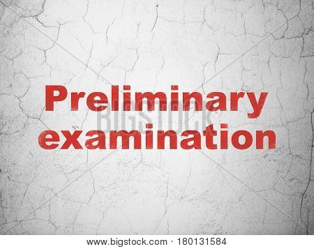 Education concept: Red Preliminary Examination on textured concrete wall background