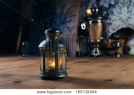 Candlestick with burning candle on the wooden floor