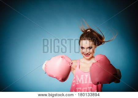 Funny girl female boxer in big fun pink gloves playing sports boxing hair motion studio shot blue background