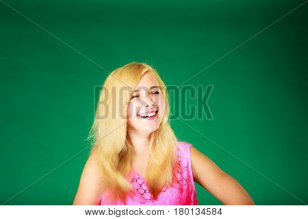 Dyeing hairstyling feminity female beauty concept. Happy blonde woman in pink top. Studio shot on green background.