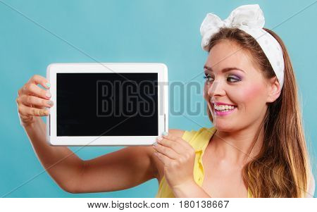 Happy smiling pin up girl holding tablet computer with blank screen copyspace. Retro woman advertising new modern technology. Old vintage fashion.