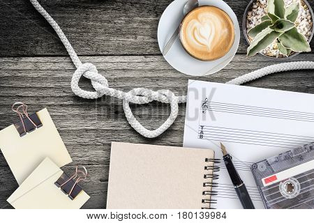 Sheet note cactus fountain pen tape cassette and coffee latte on vintage wooden table