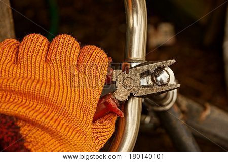 Tool in hand and iron screw on the bicycle handlebars