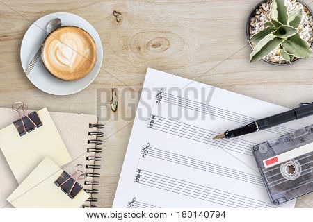 Sheet note cactus fountain pen tape cassette and coffee latte on wooden table top view picture