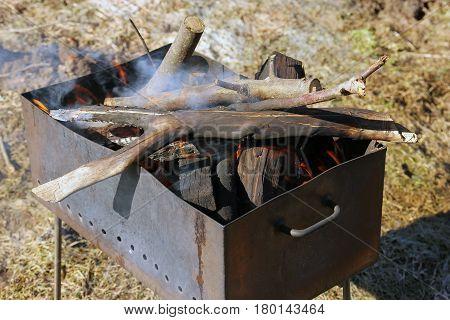 rusty iron brazier with burning firewood and smoke