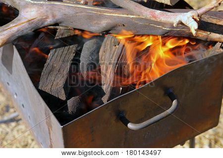 iron brazier with burning firewood with flame closeup