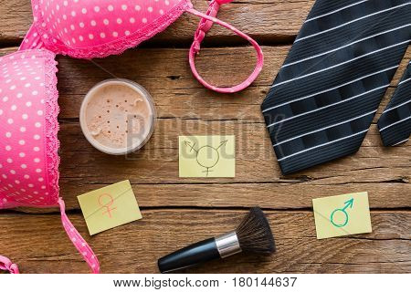 bra tie and gender symbols on wooden background
