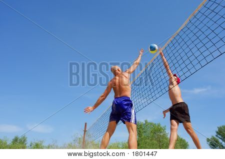 Playing Beach Volleyball - Balding Man And Teenager Compete For Ball Over Net