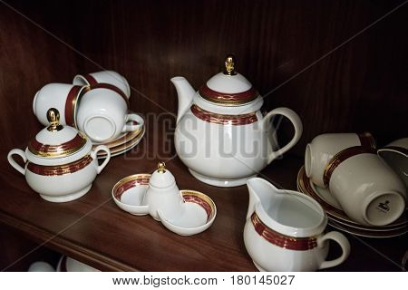 Closeup of white decorated china set of cups on wooden shelf